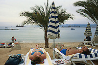 Jordan. Aqaba. Mövempick hotel. Aqaba is a holiday resort and a harbour on the Red Sea. Western tourists enjoy the sandy beach while others take a nap. Guide books (Guide du Routard, Lonely Planet) are laid on a plastic table. Merchant vessels are anchored in the Gulf of Aqaba, which is divided between three countries: Jordan, Israel and Egypt.   © 2002 Didier Ruef