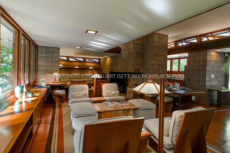 """10/9/2012--Sammamish, WA, USA..VIEW: Interior with dining table, living room area and kitchen (back right)..Architect Frank Lloyd Wright planned his """"Usonian"""" homes to be affordable for middle-class families. The 1,9500 square foot Brandes home is for sale in Sammamish, Washington (30 minutes from Seattle) at $1.39 million. It features three bedrooms, two bathrooms and a small, separate office/study space...The home was built in 1952, and has redwood trim and Wright's original furniture and some garden sculptures by Wright. It's one of only three Frank Lloyd Wright homes near Seattle...©2012 Stuart Isett. All rights reserved."""