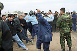 Police swinging billy clubs charge into a crowd of men waiting to apply for jobs as police officers  in Kirkuk, Iraq. Officials sought to fill 1,300 slots for the next training class, but were overwhelmed when more than 4,000 applicants showed up. More than half were turned away, and hundreds of others waited for hours, but never got a chance to submit their papers. The event was shut down after a U.S. advisor observed an Iraqi recruiting officer take a bribe from an applicant. Desperate job seekers were ordered to disperse, but many refused, so police resorted to violence to force them from the grounds. Dec. 6, 2007. DREW BROWN/STARS AND STRIPES