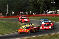 LEXINGTON, OH - JUNE 10: The Alba/Momo AR3 001/Ford of Gianpiero Moretti and Fulvio Ballabio leads a group of cars through the Carousel turn during the Lumbermen's 500 IMSA GT race at the Mid-Ohio Sports Car Course near Lexington, Ohio, on June 10, 1984.