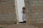 A girl watches from a doorway as U.S. soldiers and Afghan troops search nearby houses for insurgents, weapons and bomb-making materials in the city of Baqubah, Iraq, where a U.S.-led offensive is under way to clear insurgents from the city.  June 20, 2007. DREW BROWN/STARS AND STRIPES