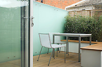 View towards the tiny table chairs and bench.  The glass wall adds a contemporary dimension to this very small garden