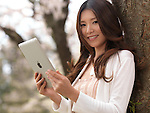 Young smiling Asian woman with iPad in a park under a cherry tree