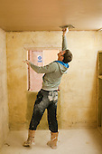 Plastering student finishes off his work using a trowel and a wet brush, Able Skills, Dartford, Kent.