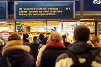 Reizigers op Utrecht CS kijken naar het informatiebord waarop te zien is dat veel treinen zijn uitgevallen of vertraagd. De eerste sneeuw in Nederland zorgt weer voor de nodige overlast. De NS heeft uit voorzorg de winterdienstregeling ingezet, waardoor veel minder treinen rijden.<br />