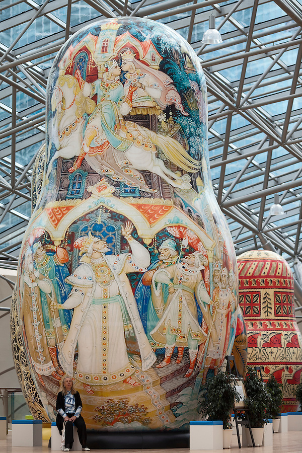 Moscow, Russia, 15/06/2011..A woman sits at an exhibition of of giant Russian matryoshki, or nesting dolls, in the newly-opened Afimall shopping centre. The dolls, designed by Boris Krasnov, are from 6 to 13 metres high, and each is decorated in a different style of traditional Russian folk art. This doll is in the Kholui style, with Mezenskaya painting style behind.