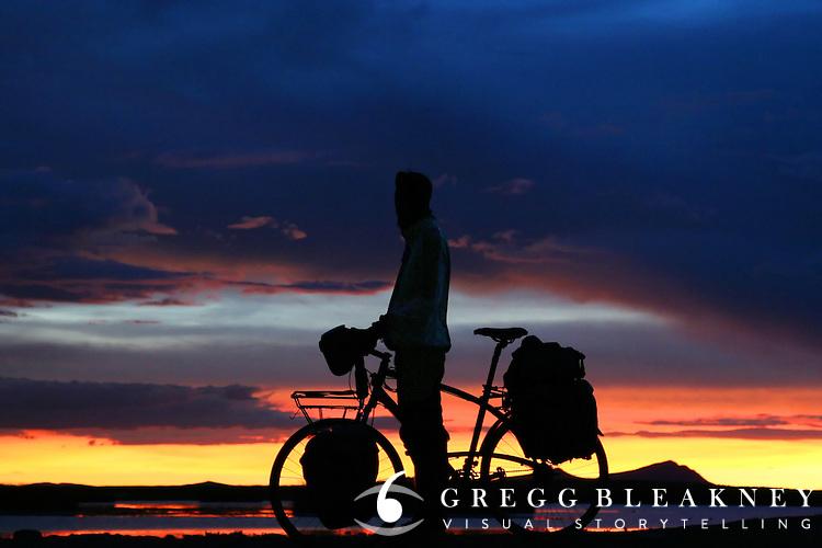 A long distance cyclist enjoys sunset over Lago Titicaca - Bolivia - South America