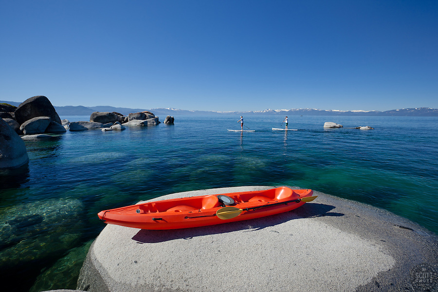 """Kayak on a Tahoe Boulder 2"" - This tandem kayak parked on a boulder was photographed near Speedboat Beach, Lake Tahoe. Two stand up paddle boarders can be seen in the distance."