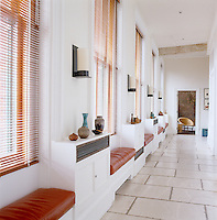 The long entrance hall is paved in limestone slabs and punctuated by a series of built-in leather-covered benches and cupboards displaying a collection of vintage ceramics