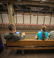 Subway riders use their tablet computers on a subway platform while waiting for a train in New York on Wednesday, September 18, 2013. (© Richard B. Levine)