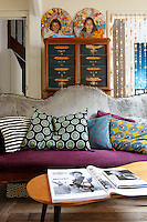 A sofa, customised by studio Nous les Anges, with cushions from Caravane in the living room; the portraits of children are by Stephanie de Beauvais