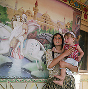 A mother and child stand beside a scene from a Persian story painted on the wall of a Roma home, in the old part of the camp.  These Arabian scenes are very popular as wall decoration, but no-one within the camp knows the reason why they were first painted.
