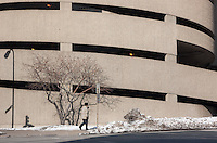 A man in a beige coat and uniform pants walks in front of a beige colored parking ramp on a cold winter day.