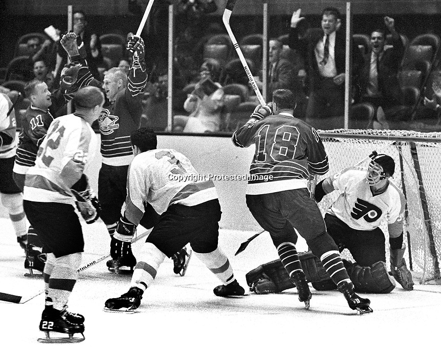 Seals score goal against the Flyers: Ron Harris arms raised, with #18 Joe Szura, flyer goalie Bernie Parent.1967 photo by Ron Riesterer
