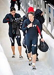18 December 2010: Shauna Rohbock (right) walks along the track dissaponited after her turnover during the second run of her 2-man bobsled for the USA, at the Viessmann FIBT World Cup Bobsled Championships on Mount Van Hoevenberg in Lake Placid, New York, USA. Neither her, not her brakeman Valerie Fleming (left) were hurt. Mandatory Credit: Ed Wolfstein Photo