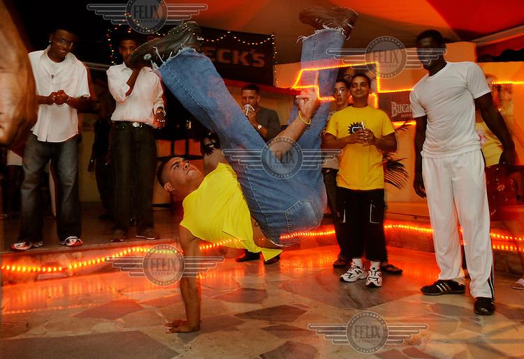 Young men breakdancing on a dance floor.