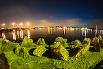 Port Washington, New York, USA. 26th June 2015. Beyond the rocks of the shoreline wall along Sunset Park, night lights shimmer on Manhasset Bay in the Gold Coast of North Shore Long Island.