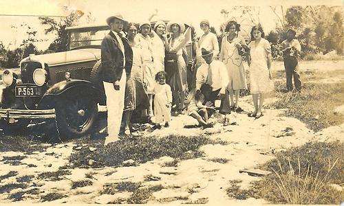 Patria Mella, al centro con pamela blanca, al lado de la puerta del auto junto a su hermano Manuel Ma. Mella del Monte. Col. YNP.