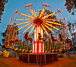 Aug. 25, 2012 - Middlebury, Connecticut, U.S.- On the Yo-Yo Super Swing, people spin around high in the air, in the brightly lit ride at night, at Quassy Amusement Park. View taken with 180 degree fisheye lens.