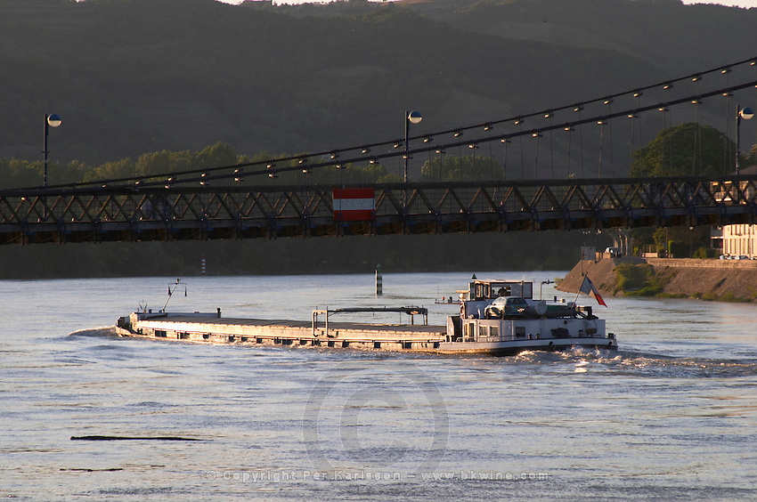barge under Passerelle Marc seguin, the cable bridge across the Rhone river hermitage rhone france