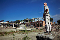 Oumar Chagaev looks out over a bombed-out factory site. Oumar, his wife, and their three children fled Grozny ten years ago during the Second Chechen War as refugees. Now as Belgian nationals they return for the first time to visit their friends, family and former home.