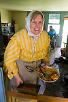 Old Bethpage, New York, U.S. 31st August 2013. CHERLY BLAM of Cedarhurst is holding pie and other baked goods she and other volunteers made during the Olde Time Music Weekend at Old Bethpage Village Restoration. The yellow dress and white lace hat she is wearing are American Civil War era clothing of the 1800's.