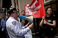 NEW YORK, NY - MAY 01: A police officer  speak with protesters during a march for immigrant worker rights as part of May Day rallies on May 1, 2013 in New York City. Rallies and marches are occuring throughout the city today to mark the day which is traditionally associated with workers movements. (Photo by Kena Betancur).