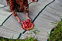 "Indonesia - Bangka Island - Rebo - A young mother serving watermelon to her family during a Friday supper. According to researches if lands are not properly reclamated the soild remains toxic and therefore vegetables and fruits which are grown will be radioactive. ""The impact of the destruction we are seeing now will last decades, if not centuries"" he predicts. ""Some species of fauna are already disappearing, as well as some high quality wood forest plants. If action is not taken now, something really bad will happen to this land."""