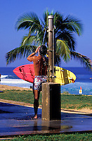 Man rinsing off after surfing at the beach showers, North Shore