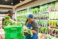 Workers trim produce in the new Whole Foods Market opposite Bryant Park in New York on opening day Saturday, January 28, 2017. The store in Midtown Manhattan is the chain's 11th store to open in the city. The store has a large selection of prepared foods from a diverse group of vendors inside the store.  (© Richard B. Levine)
