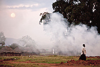 A woman walking past the smoke of a  crop burn in Madi Opei, northern Uganda. the area is populated with people displaced by the decades long conflict with the Ugandan rebel group the  Lord's resitance Army.