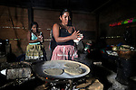 Women prepare tortillas in her home in the Guatemalan village of Santa Elena, located in the Peten region along the Salinas River where it forms a border with Mexico.