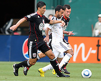 Pablo Hernandez #21 and Stephen King #20 of D.C. United hold up Juninho #19 of the Los Angeles Galaxy during an MLS match at RFK Stadium on July 18 2010, in Washington D.C. Galaxy won 2-1.