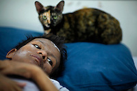 Samruei, a 35 year-old terminally ill Thai woman rests with her cat at a hospice for those dying of AIDS at a Buddhist temple Wat Prabat Nampu in Lopburi on the World AIDS day December 1, 2010. The temple's AIDS hospice is the largest of it's kind in Thailand, providing housing for HIV positive patients and palliative care for those in the final stages of the disease. Thailand has been widely praised for its work in containing the virus.   REUTERS/Damir Sagolj (THAILAND)