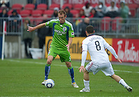 25 April 2010: Seattle Sounders defender Tyson Wahl #5 attempts to kick the ball past Toronto FC defender Dan Gargan #8 during a game between the Seattle Sounders and Toronto FC at BMO Field in Toronto..Toronto FC won 2-0....