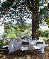 A summer lunch under the shade of a large tree where a table is covered with a floaty tablecloth and surrounded by simple folding chairs
