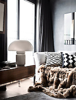 A fur blanket in the sitting room cascades off the sofa onto the parquet floor and grey rug. Floor-to-ceiling sliding doors open out onto a narrow balcony