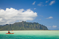 Woman paddling a red and yellow kayak in clear blue green water over Kaneohe Bay sand bar with mountains of Kualoa in the background (Puukanehoalani Mountain)