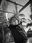 A girl hangs from the monkey bars while at recess