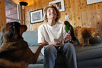Veterinary technician Toni Schriver hangs out at home with her pets, Roxy, a German shepherd-rottweiler mix; Mousy, a domestic longhaired cat; and Phoenix, an eclectus parrot. Schriver is the founder of PAWWS to Heal (Passionate Animals Working With Survivors), a nonprofit organization that uses animal therapy to help abused and physically disabled children learn appropriate behavior and boundaries. Roxy, Mousy and Phoenix are all eager volunteers in the program<br /> <br /> Client: University of Wisconsin-Madison<br /> &copy; UW-Madison University Communications 608-262-0067<br /> Photo by: Michael Forster Rothbart<br /> Date:  1/06   File#:  D100 digital camera frame 1302