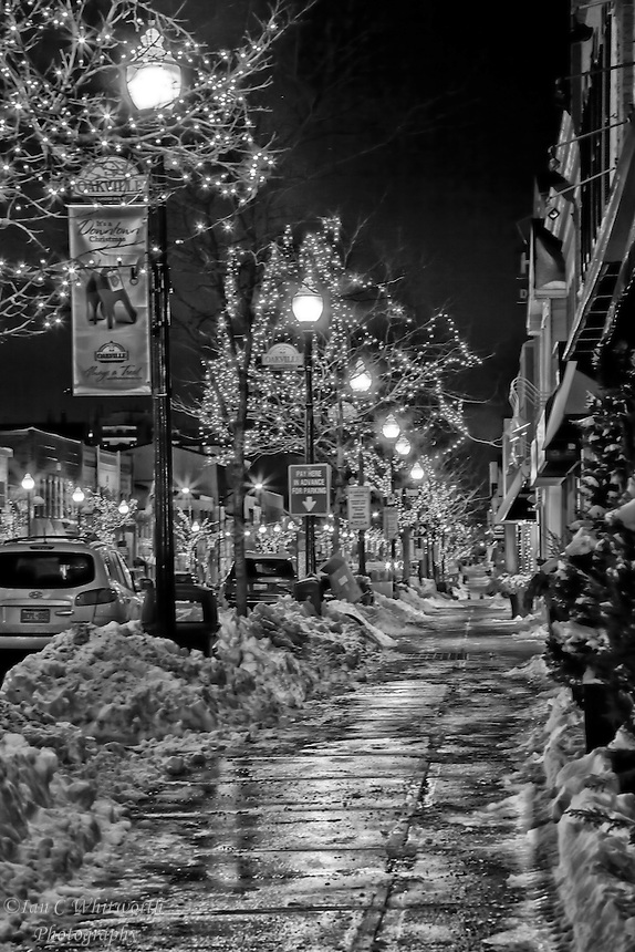 Looking down the sidewalk in downtown Oakviile at the Christmas street lights in black and white.