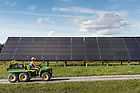 Nursery manager Lisa Dean cruises past Schoharie Valley Farms's 95-kilowatt array on August 5, 2015, with a cargo of fresh flowers.