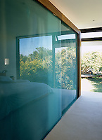 This block of wardrobes with opaque glass doors spans the central part of the room and separates the bedroom from the ensuite bathroom