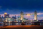 two people sit near tower bridge as night falls in london england uk