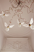 Seen against the formal stucco in the entrance hall a contemporary chandelier which is made up of a quirky jumble of wires and bare light bulbs with wings