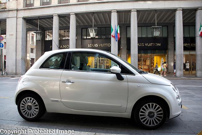 Fiat 500 car outside Louis Vuitton Shop in Via Roma Street in Turin - Torino, Italy