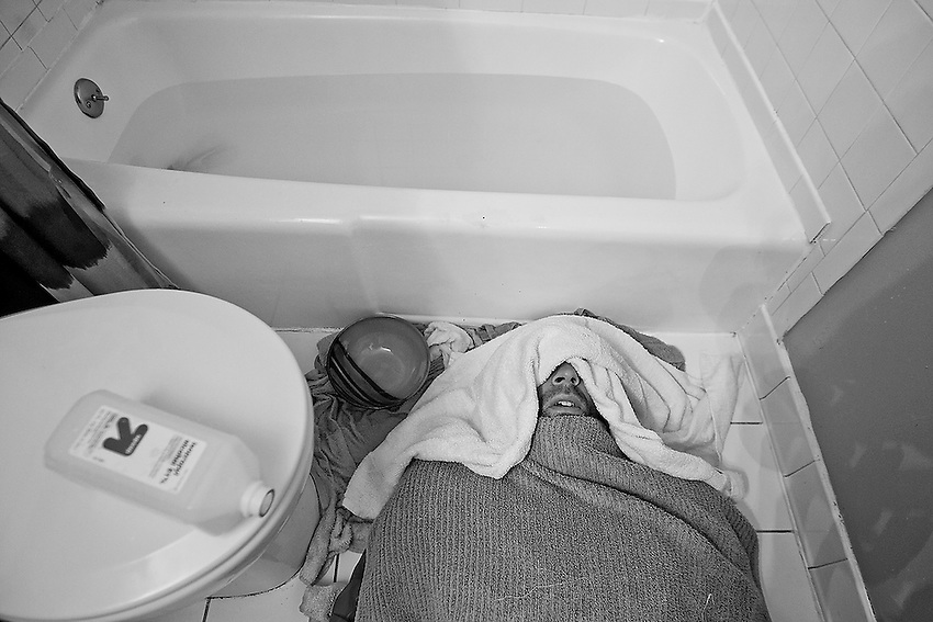 Covered in towels and wearing a rubber suit, Brick's George Sullivan lies on the bathroom floor after an epsom salt bath in scalding hot water and isopropyl rubbing alcohol in an effort to cut weight for his mixed-matrial arts fight in less than two days.