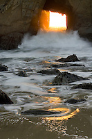 The sun sets through a window to the Pacific,  Big Sur Coast, Pfeiffer State Beach CA, USA.