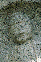 A granite Buddha image stares out at the world with eternal eyes.