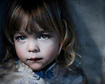 A young girl with sad eyes looking at the camera